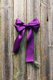 Violet satin ribbon on wooden background Stock Photography