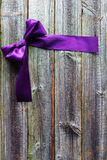 Violet satin ribbon on wooden background Royalty Free Stock Photos