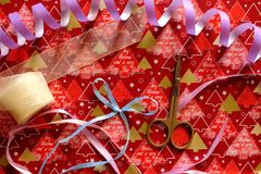 Violet serpentine with colorful ribbons and scissors on festive wrap as christmas and new year decoration. December background. Decoration for christmas Royalty Free Stock Photography