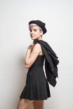 Violet short-haired woman with hat holding a coat over her shoul Stock Photos
