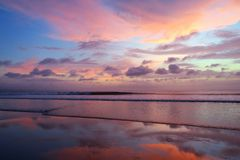 Violet sky and mirror reflection sunset at Kuta beach, Bali, Indonesia Royalty Free Stock Images