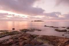 A violet sunrise on the beach of Ses figueretes, Ibiza. Spain Stock Photos