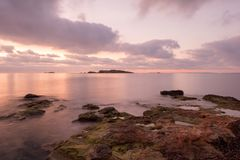 A violet sunrise on the beach of Ses figueretes, Ibiza. Spain Royalty Free Stock Photo