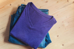 Violet t-shirt and blue denim jeans on wood Stock Images