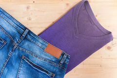 Violet t-shirt and blue denim jeans on wood Stock Photo