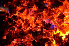 Violet tongues of flame from burning non-ferrous metals break through the hot coal. Burning chips of non-ferrous metals on coal with wood as a background Stock Photos