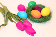 Violet tulips bouquet and colored Easter eggs Stock Photography