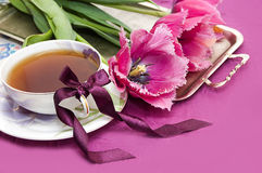 Violet tulips and cup of tea Stock Photos