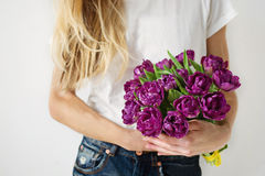 Violet tulips in girl's hands. Slim girl with long blonde hair holding violet tulips in hands Royalty Free Stock Image