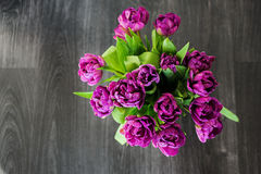 Violet tulips on the table. Violet tulips are standing on black wooden table. Top view, with place for text Royalty Free Stock Image