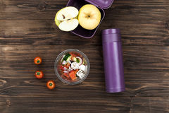 Violet vacuum bottle lying on the wooden table Royalty Free Stock Image