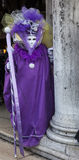 Violet Venetian Disguise. Venice, Italy-February 18,2012: Image of a person disguised in a sophisticated violet traiditional costume and mask during the Venice Royalty Free Stock Images