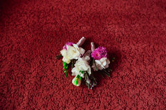 Violet and white boutonnieres lie on red carpet Stock Photos