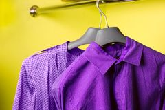 Violet women`s dress and violet men`s shirt on the hanger. Violet  women`s dress and violet  men`s shirt on the hanger, bright holiday clothes for couple, bright Royalty Free Stock Photo