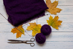 Violet yarn, knit fabric, knitting needles, scissors and yellow. Fallen leaves are on white vintage wooden desk. Top view Royalty Free Stock Images