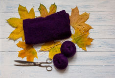 Violet yarn, knit fabric, knitting needles, scissors and yellow. Violet yarn, knit fabric, knitting needles, scissors and fallen leaves are on white vintage stock image