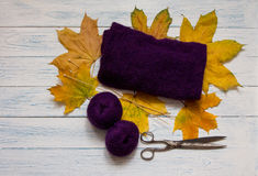 Violet yarn, knit fabric, wooden knitting needles, scissors and. Yellow fallen leaves are on white vintage wooden desk. Top view Stock Photography