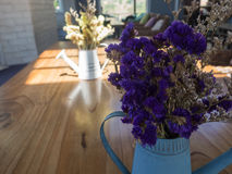 A violeta e o amarelo secaram flores na lata molhando da lata azul na madeira Imagem de Stock