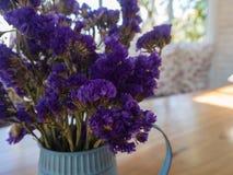 A violeta secou flores na lata molhando da lata azul na tabela de madeira Foto de Stock Royalty Free