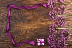 Violetblommor och en ask på träbrädet Royaltyfri Bild