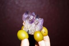 Violetkleurig kristal in de handen van groene olijfvingers stock foto's