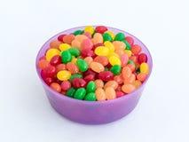 Violett bunke plast-rundaför medelformat för lösa produkter som fylls med kulöra liten-storleksanpassade sötsaker som isoleras på royaltyfria foton