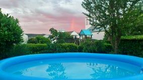 Violett himmel över blå simbassäng arkivfoton