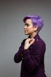 Violett-kurz-haarige Frau, die einen violetten Mantel, Händchenhalten a trägt Stockfotos