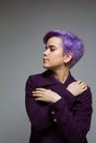 Violett-kurz-haarige Frau, die einen violetten Mantel, Kreuzungshände trägt Lizenzfreies Stockbild