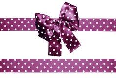 Violett pilbåge och band med vita prickar som göras från silke Arkivfoton