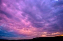 Violett solnedgång med moln royaltyfri bild