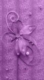 Violett vertikal handgjord hälsninggarnering med skinande pärlor, broderi, silvertråden i form av blomman och fjärilen Arkivbild