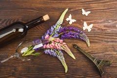 Violetta lupines i vinglaset med garneringar Arkivfoto