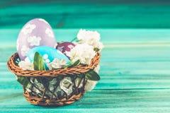Violetta och blåa easter ägg i en korg med blommor blått trä för bakgrund lyckliga easter Arkivbild