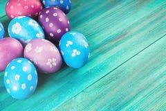 Violetta och blåa easter ägg på en blå träbakgrund lyckliga easter Royaltyfri Foto