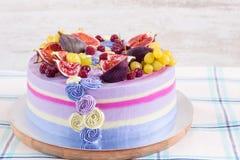 Violette en roze cake met fruit op witte houten achtergrond stock afbeelding