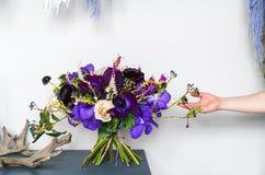 Violette Hochzeitsblumenstraußstände auf einer Tabelle im Innenraum mit den Händen eines weiblichen Floristen Wedding neigt Stockfotos