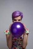 Violette kurzhaarige Frau, die einen Ballon mit ihren zwei Händen hält Stockfotos
