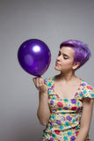 Violette kurzhaarige Frau, die einen Ballon mit ihrer Hand, Uhr hält Stockbild