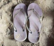 Violette Strandpantoffel auf sandigem Strand, Sommer stockfotografie