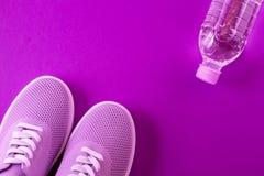 Violette Turnschuhe mit einer Flasche Wasser auf einem purpurroten Hintergrund stockfotografie
