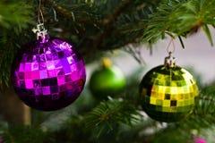 Violette und grüne Glaskugeln auf Weihnachtsbaum stockfoto