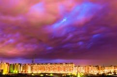 Violetter Himmel bewölkt sich nach einem Gewitter über der Nachtstadt Stockbilder