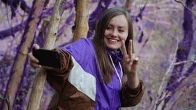Violetter Märchenwaldglückliches Mädchen in einem purpurroten olympium macht einen Frieden-selfie auf dem Hintergrund von dem moo stock video
