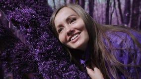 Violetter Märchenwaldglückliches Mädchen in einer lila Jacke berührt das weiche dichte purpurrote Moos auf einem Baum und Lächeln stock video
