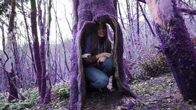 Violetter Märchenwaldlustiges Mädchen versteckt sich in einer Höhle des alten Baums und betrachtet ihn mit dem Interesse und scha stock video footage