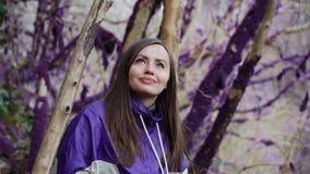 Violetter Märchenwaldsüßes Mädchen in einer farbigen Jacke betrachtet die ungewöhnlichen moosbedeckten Bäume in den Märchen stock video