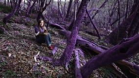 Violetter Märchenwaldschönes Mädchen in einer lila Jacke sitzt in einem fabelhaften lila Wald und in den Blicken an der Blume in  stock footage