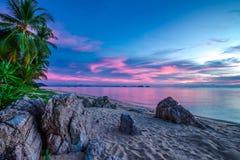 Violetter Sonnenuntergang über dem Meer und dem felsigen Strand Lizenzfreies Stockfoto