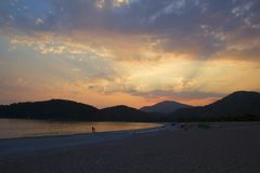 Violetter Sonnenuntergang an der Küste mit Bergen auf Hintergrund Sun-Br?che durch Wolken Purpurroter Dämmerungssommer relax lizenzfreies stockbild